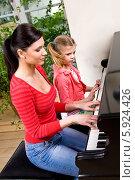 Купить «Мама с дочерью играют на рояле в четыре руки», фото № 5924426, снято 24 ноября 2017 г. (c) Joanna Malesa / Фотобанк Лори