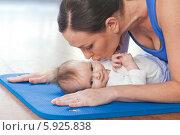 Молодая мама целует малыша на коврике в спортзале. Стоковое фото, агентство BE&W Photo / Фотобанк Лори