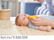 Мама очищает носик ребенка с помощью аспиратора. Стоковое фото, агентство BE&W Photo / Фотобанк Лори