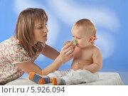 Мать дает заболевшему ребенку лекарство из мерного стаканчика. Стоковое фото, агентство BE&W Photo / Фотобанк Лори