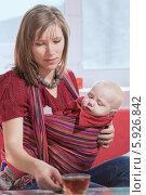 Купить «Молодая женщина с малышом в слинге пьет чай», фото № 5926842, снято 8 апреля 2014 г. (c) Юрий Викулин / Фотобанк Лори