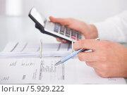 бизнесмен делает подсчеты на калькуляторе, фото № 5929222, снято 21 февраля 2014 г. (c) Андрей Попов / Фотобанк Лори