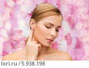 Купить «Красивая девушка дотрагивается до уха, наклонив голову на фоне розовых цветов», фото № 5938198, снято 5 декабря 2013 г. (c) Syda Productions / Фотобанк Лори