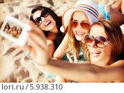 Купить «Веселые подруги фотографируются на пляже», фото № 5938310, снято 11 июля 2013 г. (c) Syda Productions / Фотобанк Лори