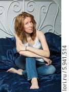 Купить «Девушка в джинсах сидит на кровати», фото № 5941514, снято 12 июня 2013 г. (c) Михаил Ворожцов / Фотобанк Лори