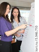 Купить «женщины изучают график», фото № 5946710, снято 13 февраля 2010 г. (c) Phovoir Images / Фотобанк Лори