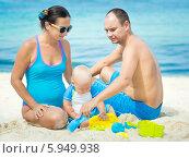 Купить «Семья в синей одежде сидит на пляже», фото № 5949938, снято 17 апреля 2014 г. (c) Ольга Хорошунова / Фотобанк Лори