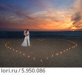 Влюбленная пара стоит на пляже в окружении свечей составленных в форме сердца. Стоковое фото, фотограф Елена Кирьян / Фотобанк Лори
