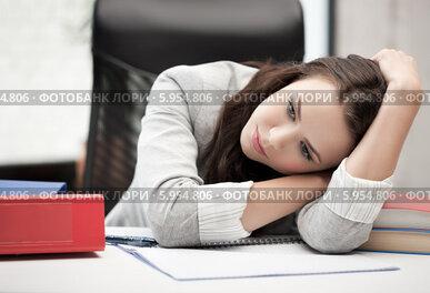 Уставшая женщина положила голову на руки, сидя за рабочим столом в офисе