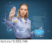 Купить «Серьезная девушка держит в руке планшетный компьютер, работая с виртуальным экраном», фото № 5955146, снято 17 ноября 2012 г. (c) Syda Productions / Фотобанк Лори