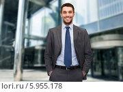 Купить «Позитивный бизнесмен в расстегнутом пиджаке стоит, засунув руки в карманы брюк, рядом с офисным зданием», фото № 5955178, снято 28 июня 2013 г. (c) Syda Productions / Фотобанк Лори