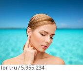 Купить «Молодая женщина с ухоженной кожей трогает ухо, слегка наклонив голову на фоне моря», фото № 5955234, снято 5 декабря 2013 г. (c) Syda Productions / Фотобанк Лори