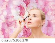 Купить «Ухоженная девушка красит ресницы тушью на розовом цветочном фоне», фото № 5955278, снято 5 декабря 2013 г. (c) Syda Productions / Фотобанк Лори