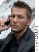Серьезный молодой мужчина с мобильным телефоном. Редакционное фото, агентство BE&W Photo / Фотобанк Лори