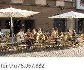 Люди сидят в уличном европейском кафе в лучах заходящего солнца (2008 год). Редакционное фото, фотограф Татьяна Чечина / Фотобанк Лори