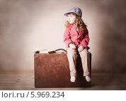 Купить «Девочка сидит на старом чемодане», фото № 5969234, снято 30 апреля 2014 г. (c) Майя Крученкова / Фотобанк Лори