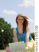 Купить «Красивая рыжеволосая девушка с ноутбуком сидит на зеленом лугу», фото № 5970130, снято 10 июля 2020 г. (c) BE&W Photo / Фотобанк Лори