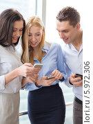 Купить «Коллеги в офисе общаются, просматривая новости на экране смартфона», фото № 5972306, снято 23 ноября 2013 г. (c) Syda Productions / Фотобанк Лори