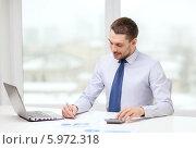 Купить «Молодой бизнесмен в рубашке и галстуке работает, сидя за столом в офисе», фото № 5972318, снято 15 марта 2014 г. (c) Syda Productions / Фотобанк Лори