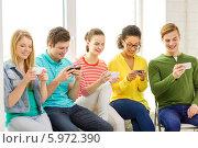 Купить «Счастливые молодые люди улыбаются, сидя на подоконнике со смартфонами», фото № 5972390, снято 29 марта 2014 г. (c) Syda Productions / Фотобанк Лори