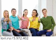 Купить «Группа улыбающихся молодых людей показывает жест одобрения, сидя на подоконнике», фото № 5972402, снято 29 марта 2014 г. (c) Syda Productions / Фотобанк Лори
