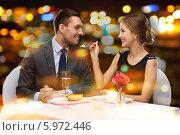 Купить «Влюбленная пара в ресторане. Девушка дает попробовать десерт молодому человеку», фото № 5972446, снято 9 марта 2014 г. (c) Syda Productions / Фотобанк Лори