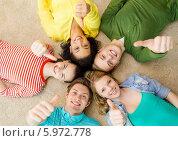 """Друзья лежат на полу, соприкоснувшись головами, и показывают жест """"все отлично"""" Стоковое фото, фотограф Syda Productions / Фотобанк Лори"""