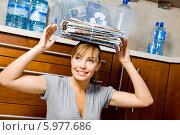 Девушка собирает старые газеты для сдачи в макулатуру. Стоковое фото, агентство BE&W Photo / Фотобанк Лори