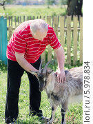 Купить «Пожилой мужчина ухаживает за козой», фото № 5978834, снято 17 мая 2014 г. (c) Майя Крученкова / Фотобанк Лори