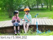 Купить «Два мальчика с самокатом и роликами отдыхают, сидя на деревянном помосте в парке», фото № 5984202, снято 7 июня 2014 г. (c) Юлия Кузнецова / Фотобанк Лори