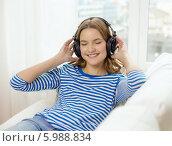 Купить «Девушка в наушниках с милой улыбкой слушает музыку, закрыв глаза», фото № 5988834, снято 26 февраля 2014 г. (c) Syda Productions / Фотобанк Лори