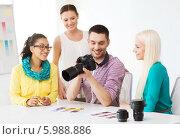 Купить «Молодые сотрудники в офисе обсуждают вместе с фотографом сделанные фотографии», фото № 5988886, снято 17 мая 2014 г. (c) Syda Productions / Фотобанк Лори