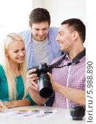 Купить «Молодые сотрудники в офисе обсуждают результаты работы фотографа», фото № 5988890, снято 17 мая 2014 г. (c) Syda Productions / Фотобанк Лори