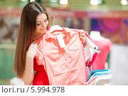 Купить «Красивая девушка с длинными волосами в красном платье делает покупки, разглядывает одежду в магазине», фото № 5994978, снято 10 июня 2014 г. (c) Вера Франц / Фотобанк Лори