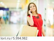 Купить «Красивая девушка с длинными волосами в красном платье делает покупки, держит пакеты и разговаривает по телефону», фото № 5994982, снято 10 июня 2014 г. (c) Вера Франц / Фотобанк Лори