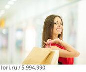 Купить «Красивая девушка с длинными волосами в красном платье делает покупки, держит пакеты», фото № 5994990, снято 10 июня 2014 г. (c) Вера Франц / Фотобанк Лори