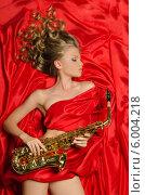 Купить «Красивая молодая девушка с саксофоном на красной ткани», фото № 6004218, снято 5 июня 2014 г. (c) Заметалов Андрей / Фотобанк Лори