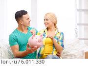 Купить «Мужчина и женщина со свиньей-копилкой в новой квартире», фото № 6011330, снято 16 февраля 2014 г. (c) Syda Productions / Фотобанк Лори