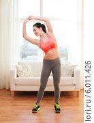 Купить «Утренняя гимнастика. Улыбающаяся девушка делает зарядку дома», фото № 6011426, снято 1 апреля 2014 г. (c) Syda Productions / Фотобанк Лори