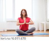 Купить «Девушка в красной футболке медитирует дома, сидя, скрестив ноги, на специальном коврике», фото № 6011670, снято 19 марта 2014 г. (c) Syda Productions / Фотобанк Лори