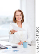 Купить «Молодая бизнес-леди с улыбкой протягивает документ, сидя за столом в офисе», фото № 6011906, снято 18 июля 2013 г. (c) Syda Productions / Фотобанк Лори