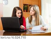 Купить «Две девушки смотрят в документы перед экраном ноутбука дома», фото № 6024710, снято 21 марта 2014 г. (c) Яков Филимонов / Фотобанк Лори
