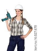 Купить «радостная девушка в каске держит электродрель», фото № 6027670, снято 17 февраля 2011 г. (c) Phovoir Images / Фотобанк Лори
