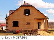 Фасад недостроенного одноэтажного дома из желтого кирпича с мансардой на фоне голубого неба с белыми облаками. Стоковое фото, фотограф Анна Пикунова / Фотобанк Лори