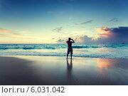 Мужчина стоит на вечернем пляже и фотографирует закат на мобильный телефон. Стоковое фото, фотограф Iakov Kalinin / Фотобанк Лори