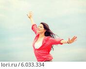 Счастливая девушка с развевающимися волосами стоит, раскинув руки в стороны. Стоковое фото, фотограф Syda Productions / Фотобанк Лори