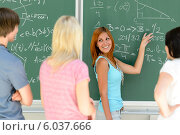 Students standing front of green chalkboard math. Стоковое фото, фотограф CandyBox Images / Фотобанк Лори