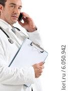 Купить «Doctor on phone with clipboard», фото № 6050942, снято 18 июня 2010 г. (c) Phovoir Images / Фотобанк Лори