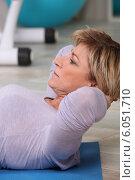 Купить «Woman doing sit-ups on gym mat», фото № 6051710, снято 13 апреля 2010 г. (c) Phovoir Images / Фотобанк Лори