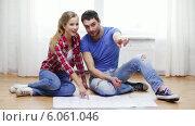 Купить «Smiling couple discussin blueprint at home», видеоролик № 6061046, снято 31 января 2014 г. (c) Syda Productions / Фотобанк Лори